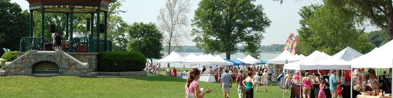 Festival tents, lake, gazebo, and crowd